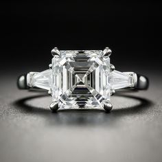 Impressive in both quality and scale, this hand fabricated platinum engagement ring features an ice-white square emerald-cut (aka Asscher-cut) diamond, accompanied with a GIA grading report indicating E color and VS2 clarity. The spectacular diamond is traditionally presented between a duo of perfectly color matched tapered baguettes. A simply sparkling, high caliber classic. Currently ring size 4 1/2.