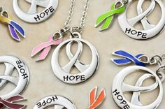 "Give the gift of hope with our Ribbon of Hope Necklace with Cancer Awareness Ribbon Charm. It hangs on an 18"" chain with a lobster closure and includes one of our exclusive ribbon charms in the cancer color of your choice. Beautifully boxed and ready for gift giving."