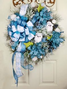 Handmade Christmas Blue Snow Pine Owl Wreath - White Owl Snowflake Wreath - Blue Glittered Poinsettia Snowflake Owl Wreath - Blue Christmas Wreath. This lovely blue snowflake owl wreath is perfect for Christmas and winter both! The base of this wreath is thick and lush snow pine with large pine cones. The wreath has beautiful blue glittery ribbons with one having snowflakes on it, one having blue zebra stipes, and one a solid sheer blue. Dotted throughout the wreath are sparkling…