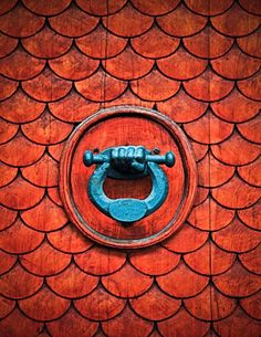 Pretty latch on a fish scale door .