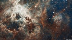 About 160,000 light-years away lies the brightest star-forming region in our part of the Universe, within the Tarantula Nebula. This picture is one of the largest composites ever assembled from Hubble Space Telescope images, and has been combined with data from Eso's 2.2m telescope, released to celebrate Hubble's 22nd anniversary.
