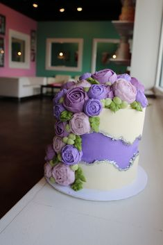 Purple and white fault line cake with silver accents and buttercream flowers by 3 Sweet Girls Cakery. This cake is perfect for any occasion!