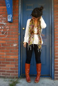 easy to recreate: denim skinny jeans, cream button sweater, skinny belt and multicolored scarf with cognac boots.