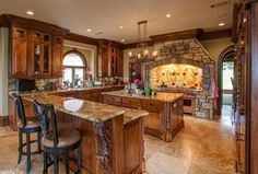 Mediterranean Kitchen with Kitchen island, Oil rubbed bronze pot filler, Complex Granite, U-shaped, Raised panel, Custom hood