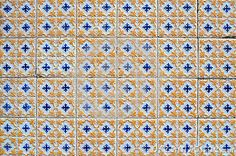 (C) Celia Ascenso - Vintage portuguese textured blue and yellow tiles on an exterior wall on Figueira da Foz, Portugal.