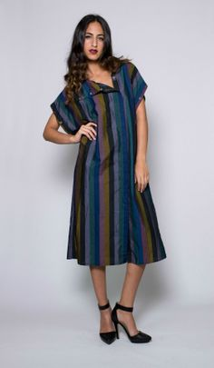 This dark jewel tone vintage dress is versatile and cross seasonal. Complete with heavy metal hardware snaps and sleeves that detach. This asymmetric style dress is bold and practical, and perfect for the girl on the go. #snapdress #vintagedress #versatiledress #stripeddress #jeweltone #shortsleevedress #longsleevedress #vintagefashion #onlinevintage #vintageclothing