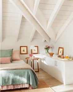 Dormitorio abuhardillado con ropa de cama en rosa y verde