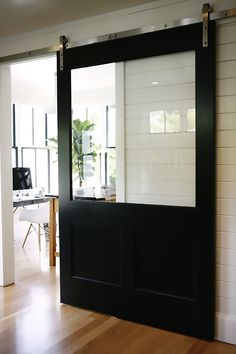 Black sliding barn door with large glass panel