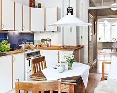 Esta cozinha pequna foi decorada com armarios de madeira rustica com portas de cor branca