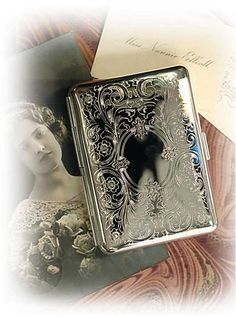 "SILVER PLATED CALLING CARD CASE Replicated from an antique German cigarette case, this ornately embellished silverplate accessory is ideally suited for credit cards and business cards. An elasticized inner band secures the contents on both sides. 2.5 x 3.5"". VTC Exclusive!"