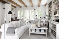 Great balance - bright white and dove grey with warmth of books and wood beams.