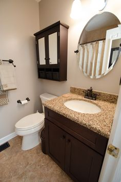 Small vanity with medicine cabinet, granite countertop, oval mirror, complete bathroom remodel - brought to you by Re-Bath of the Triangle.