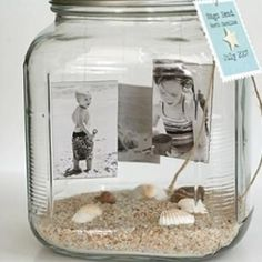 I love photos in glass vases and mason jars, and I've seen them with vacation beach sand, but this one's a cool idea:  dangle the photos from the lid floating ABOVE the sand........photo memory jar