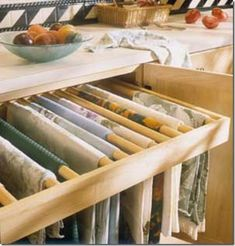 A pullout drawer fitted with dowel rods makes for a great wrinkle-free way to store linens.