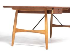"Hans J. Wegner: ""JH 571"". A solid teak desk, mounted on slightly oblique oak legs. Brass stretchers, drawer mounting and handles. Made by Johannes Hansen."