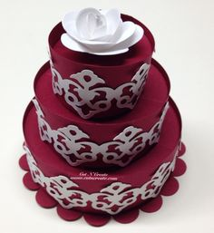 A red 3D cake with white damask detailing and a handmade white rose. These are for the inside of exploding box wedding invitations! Oh my!  Custom orders welcome!  www.cutncreate.com http://facebook.com/CutnCreate