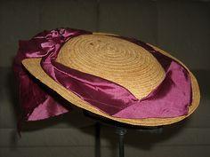 late 1860s; It is a woven straw oval bonnet trimmed in purple stripe silk ribbon.  It has a gauze lining.