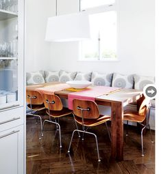 Banquet seating, Eames chairs, rustic wood table. Dining room!