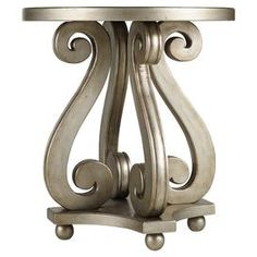 """Display a vase of lush blossoms and framed family photos atop this elegant wood accent table, showcasing an openwork scrolling base and a silver-hued finish.  Product: Accent tableConstruction Material: Hardwood solids and resinColor: Brown and silverFeatures: Openwork scrolling baseDimensions: 26.25"""" H x 24"""" Diameter"""
