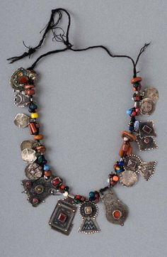 Morocco - Tagmout necklace worn by the Ida ou Kessous and Ida ou Nadif people. Silver pendants, some with niello, stone or glass cabochons, combined with amber, coral, stone and glass beads, on a wool cord.