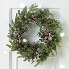 couronne de Noël naturelle en branches de sapin, feuilles vertes et pommes de pin givrées