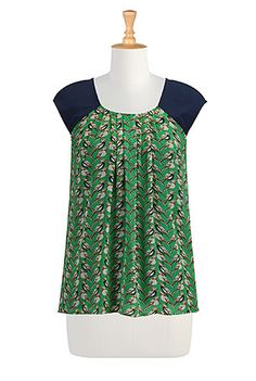 Colorblock shoulders and a pleated scoop neck tops this soft flowing blouse in whimsical bird print chiffon