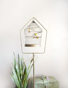 This is an antique Hendryx metal bird cage with the original stand. The pagoda shape cage detaches from the tray with small hooks (see second to