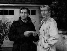 Perry and Paul in raincoats, outside a garage at night