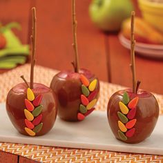 "Fall-colored candy ""leaves"" highlight these easy-to-make caramel apples. Decorate them using Wilton® Caramel Dip and Wilton Turkey Cookie Decorating Kit."