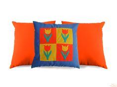 Capa de almofada em sarja azul claro com quadrado de tulipas (patchwork) em malhas diversas. Mais 2 capas em sarja laranja.