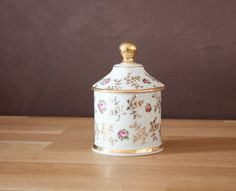 Small antique porcelain floral-and-gold-design canister.
