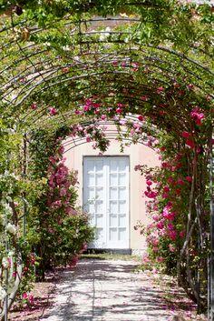 O arco de flores na entrada desta casa dá um tom muito romântico ao lugar.