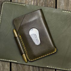 Leather patina or how leather ages. My personal notebook compact wallet in aged Olive compared to a new piece of the same color underneath. Free Notebook, Pocket Notebook, Small Wallet, Zip Around Wallet, Broken Finger, Space Pen, Personalized Notebook, Leather Notebook, Credit Card Wallet
