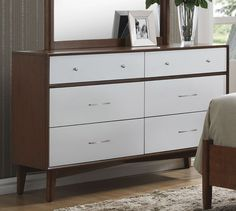Add storage and mid-century modern style to your bedroom with this six drawer dresser. Spacious drawers allow you to easily organize folded clothes, bedding and more within the confines of your bedroom. This dresser features a white wood finish on the drawer fronts and a golden brown on the rest of the piece. Pair with a coordinating mirror for more style and function.