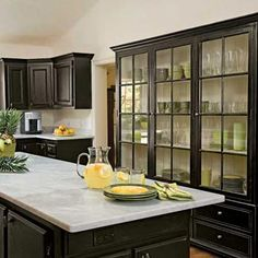 Despite black being a traditionally heavy color, the glass front cabinets really lighten the space and make for quite a beautiful display area.... assuming of course you have cute dishes.
