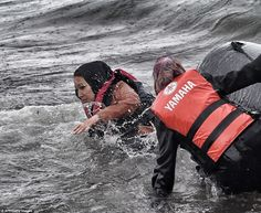 Two migrant women scramble for the shore after their rubber dinghy nears the Greek island of Lesbos