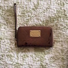 Michael Kors Wristlet Brown/Gold Great wallet. Great condition with some small scratches on the front plate. Zipper works. Michael Kors Bags Clutches & Wristlets