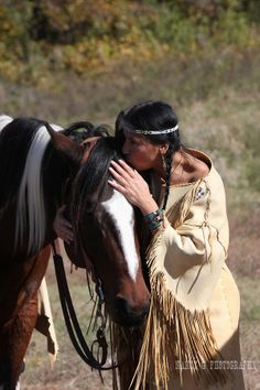 A Native American Indian woman talking to her horse