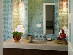 This+guest+bathroom+features+a+gorgeous+aqua+tile+backsplash.+Two+tiled+niches+on+either+side+of+the+mirror+provide+storage+space+for+towels+and+glass+pendants+give+the+space+a+soft+glow.