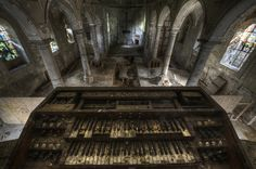 The skeletal keys of a decaying organ overlook a forgotten hall of worship rinsed in pale light from intricately crafted stained glass windows