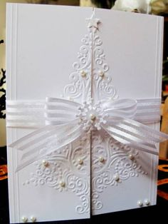 all white embossed  Christamas tree on gatefold card with pearl embellishmets and cute snowflake on the closure bow...absolutely gorgeous!!!
