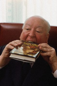 "Alfred Hitchcock literally devouring Tom Prideaux's ""Love or Nothing: The Life and Times of Ellen Terry."""