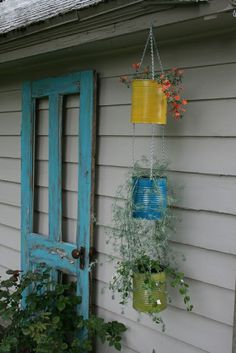 Dishfunctional Designs: The Upcycled Garden Spring 2013 ~ Love this, the colored door and the coffee can flower hanging planters ~ so simple ~ so neat!