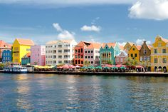 Willemstad, Curacao  The legend goes that when the Dutch still ruled the island in the 1800s the governor at the time suffered from migraine headaches, that he attributed to the Caribbean sun. He decreed that the residents paint buildings and other structures anything but white. Now we've got a World Heritage Site with buildings in blues, yellows, pinks and reds with white trim. The Most Colorful Places in the World