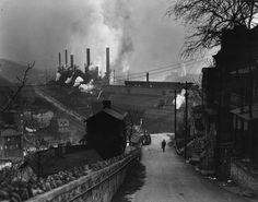 Hillside houses overlook smoke-belching steel mills in...