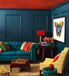 love these blue walls and all the happy color....couch, yellow chair and that cute little table in the corner. SMILE!