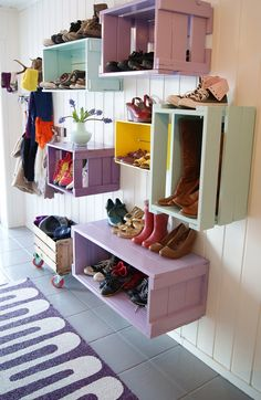 We normally think that storage in a mud room space needs to sit on the floor - i love how these colorful crates hang vertically and horizontally to hold a range of objects -- even riding boots!