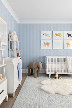 A white sheepskin rug is layered over and ivory and blue rug placed beneath an Oeuf Sparrow Crib placed next to an RH Baby & Child Oversized Wool Felt Elephant and under framed watercolor art hung from a vertical blue stripe wallpapered wall. Baby Boy Room Decor, Baby Room Design, Baby Boy Rooms, Nursery Design, Baby Boy Nurseries, Kids Rooms, Baby Boys, Nursery Room, Kids Bedroom