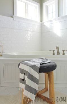 Love the subway tile, classic small windows and wainscoting tub surround of this white master bath.