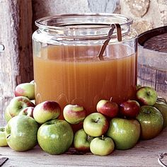 Serve homemade apple cider in a glass jar with fresh apples surrounding it.